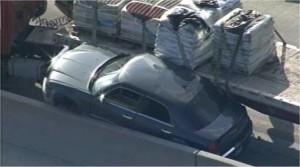 18-wheeler wreck pins car against concrete center divider
