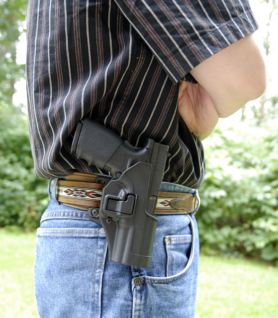Vertical of a belt mounted rigged holster holding a semi automatic pistol.